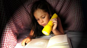 girl reading in bed flashlight